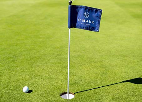 Blue St. Mark Golf flag in hole with golf ball next to it