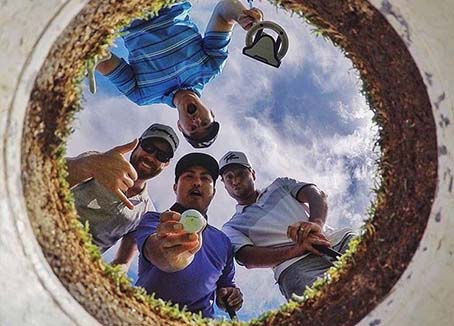 Golfers looking into a hole